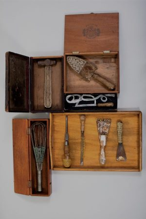 Series of old tools embellished with textiles set into wooden boxes