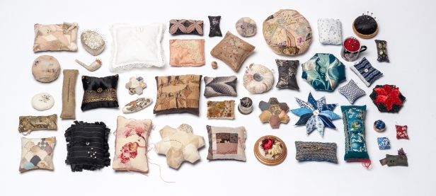 image of 46 decorative pincushions arranged for exhibition