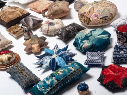 image of a group of over 25 decorative pincushions arranged for exhibition